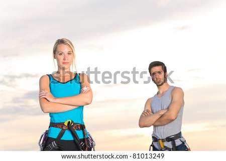 Rock climbing active young mountaineers reach top at sunset - stock photo