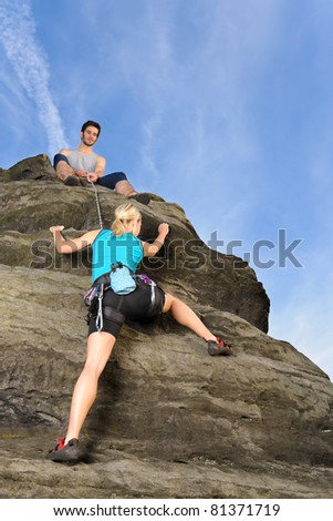 Rock climbing active young woman  man holding rope on top - stock photo