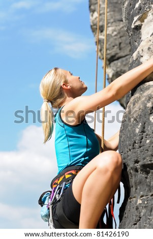 Rock climbing blond woman on rope  sunny day - stock photo
