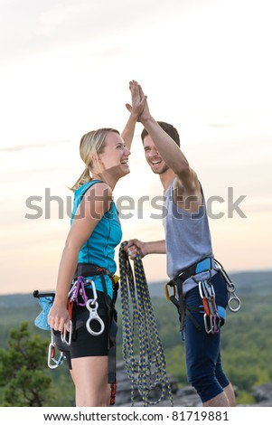Rock climbing cheerful active young mountaineers reach top at sunset - stock photo