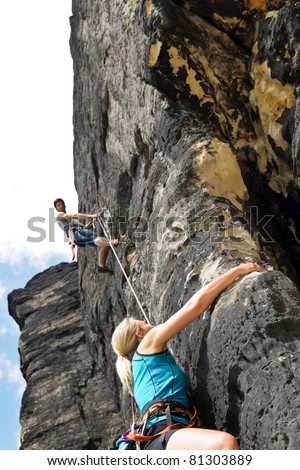 Rock climbing male instructor hold rope blond woman hanging - stock photo