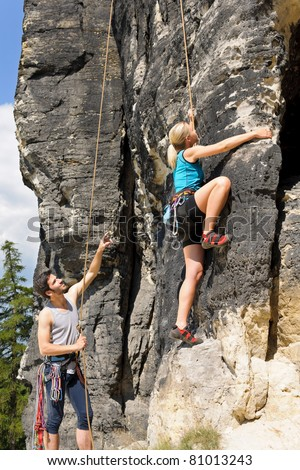 Rock climbing male instructor hold rope blond woman sunny day - stock photo