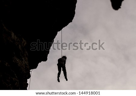Rock climbing silhouette - stock photo
