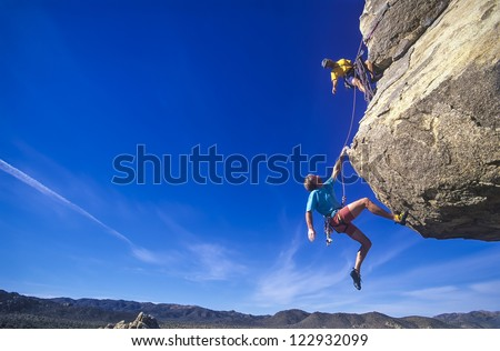 Rock climbing team struggle for success on a challenging ascent. - stock photo