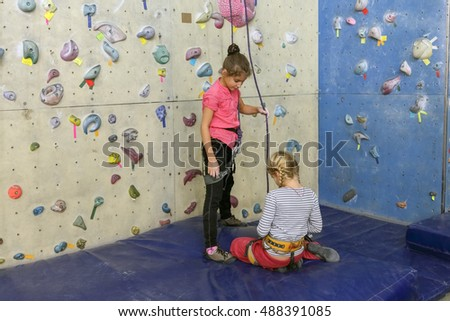 Rock climbing. two girls in indoor climbing center, one of them attaches himself to safety system.