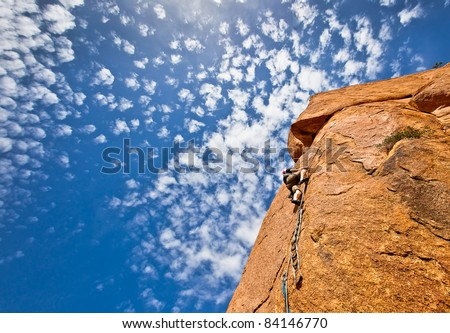 rock climbing:young climber on a steep granitic mountain over a blue sky - stock photo