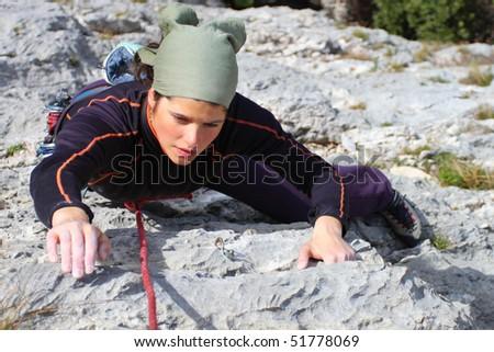 Rock climbing. Young woman climbing a limestone rock - stock photo