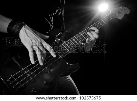 rock concert: bass guitarist playing on stage - stock photo