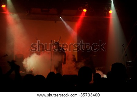 Rock concert, blurred unrecognizable musicians on the stage - stock photo