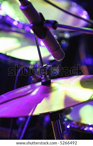 Rock concert series: drum set with microphone, lit by purple and green - stock photo