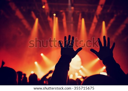 Rock concert, silhouette of raised up man's hands over bright red lights, people having fun in night club, dancing and listening music - stock photo