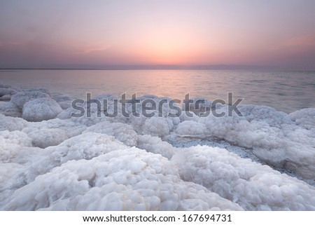 Rock covered with salt on coast of Dead sea, Jordan in sunset scenary - stock photo