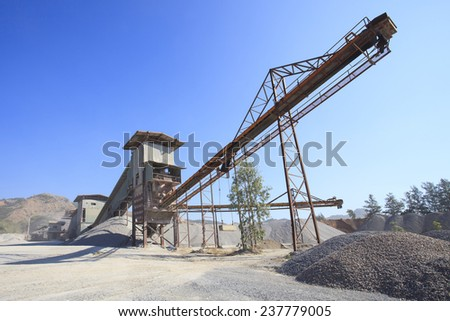 rock crusher machine industry chain moving to logistic gravel use for construction matterial and pollution of heavy industry  - stock photo