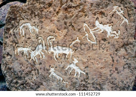 Rock drawings of hunting story on a carved stone in Timna Park, Israel. - stock photo