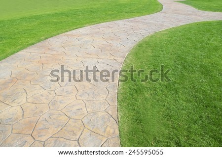 Rock footpath in the middle of a lawn field - stock photo