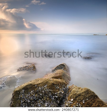 Rock formation cover with green moss and barnacle pointing to the sea at morning with blue cloudy sky - stock photo