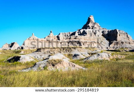 Rock Formations in Grassy Field at Badlands National Park - stock photo