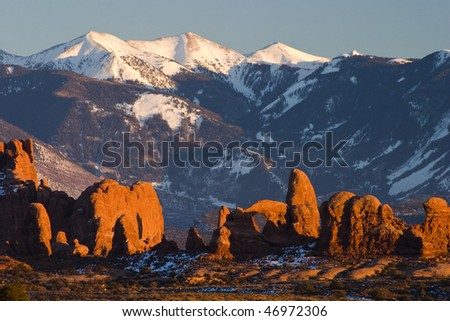Rock formations in morning sunlight with Manti La Sal mountains in background, Arches N.P., Utah - stock photo