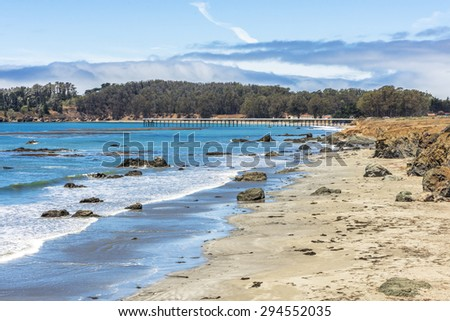 Rock, geological formations, and San Simeon Pier along the rugged Big Sur coastline, near Cambria, CA. on the California Central Coast. - stock photo