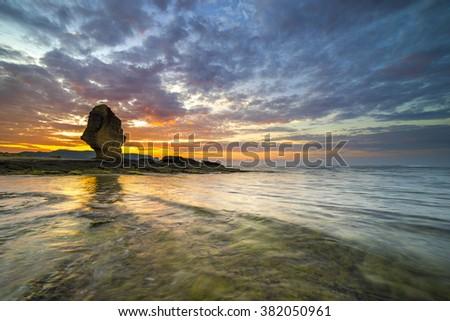 Rock green moss with sunrise background at Pantai Batu Payung ( Umbrella Rock Beach) lombok, Indonesia.  - stock photo