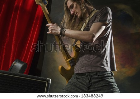 rock guitar player on stage with amp - stock photo