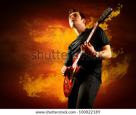 Rock guitarist play on the electric guitar around fire flames