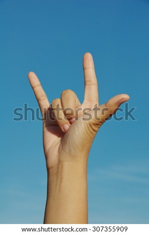 rock hand sign blue background - stock photo
