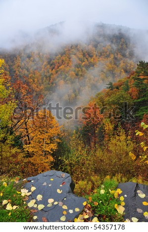 Rock ledge looking down into a cloud filled valley in New York State - stock photo