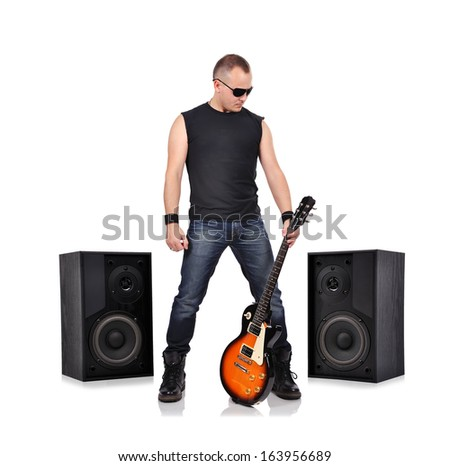 rock musician holding electrical guitar and big speakers - stock photo