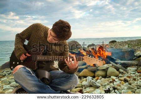 rock musician .Inviting campfire on the beach during the summer - stock photo