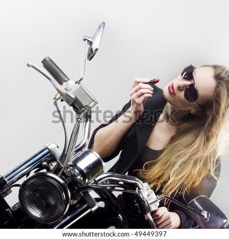 Rock'n'roll girl, The girl paints lips sitting on a motorbike - stock photo