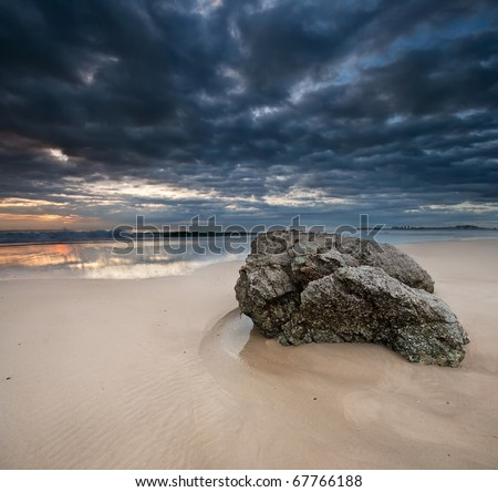 Rock on the beach with dramatic sky on square format - stock photo