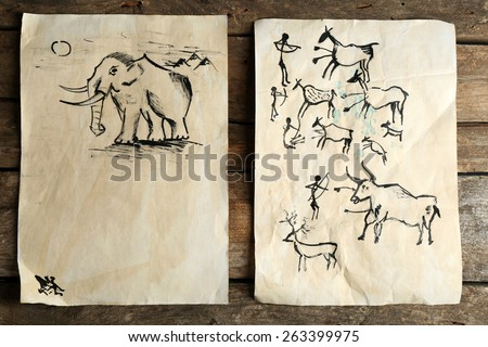 Rock paintings on paper on wooden background - stock photo
