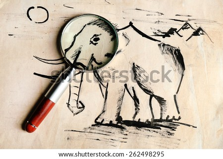 Rock paintings with magnifier on paper close up - stock photo