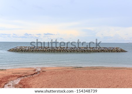 rock pier/breakwater at pattaya beach - stock photo