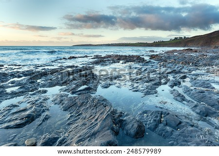 Rock pools at low tide on Pendower Beach in Cornwall - stock photo