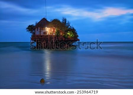 Rock romantic restaurant in Indian ocean near Zanzibar coastline - stock photo