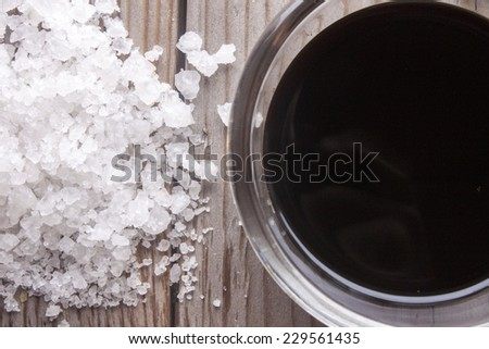 Rock salt and soy sauce, on wooden background - stock photo