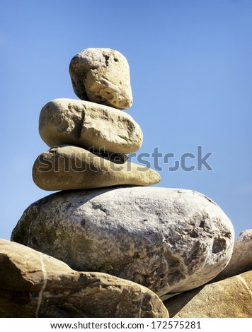 rock stack in front of blue sky - stock photo