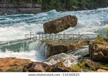 Rock stands against the force of intense white-water rapids in the Niagara river. - stock photo