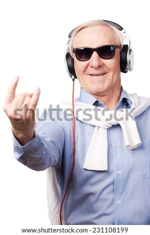 Rock star. Cheerful senior man in headphones listening to music and showing hand sign while standing against white background  - stock photo