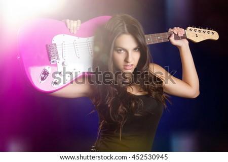 Rock star girl holding guitar - stock photo