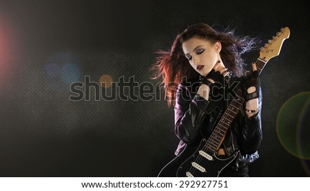 Rock star posing with electric guitar - stock photo