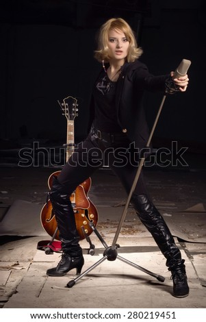 Rock star singing into a microphone on industrial background