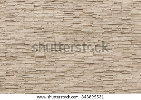 Rock stone brick tile wall aged texture detailed pattern background in dark sepia cream  brown color tone: Grunge ancient rustic limestone patterned backdrop for decoration in tan brown toned colour - stock photo