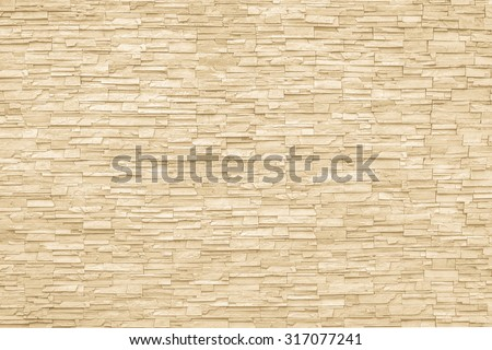 Rock stone brick tile wall aged texture detailed pattern background in light cream beige brown color tone: Grunge ancient rustic limestone patterned backdrop for decoration in creme brown toned colour - stock photo
