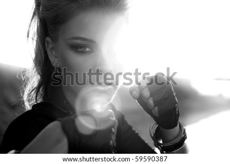 Rock style girl in an aggressive posture in the rays of bright sunshine - stock photo