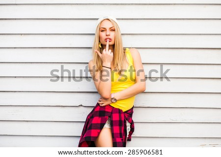 Rock style hipster girl in hat posing on wall background. A young blonde wearing a yellow jersey, shorts and white hat. On the belt hanging red plaid shirt - stock photo
