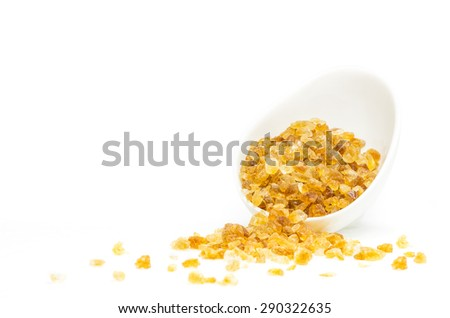 Rock sugar from sugar cane in white cup on white background. - stock photo