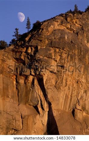 Rock wall, granite cliff at sunset and moonrise, in Yosemite National Park, California, USA - stock photo
